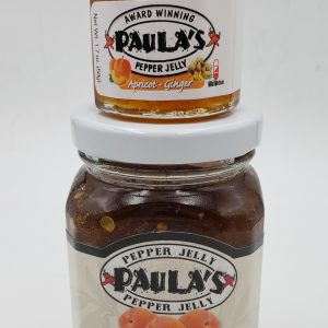 The 1.7 oz. pepper jelly jar on top of the 8 oz. pepper jelly jar from Paula's Pepper Jelly.
