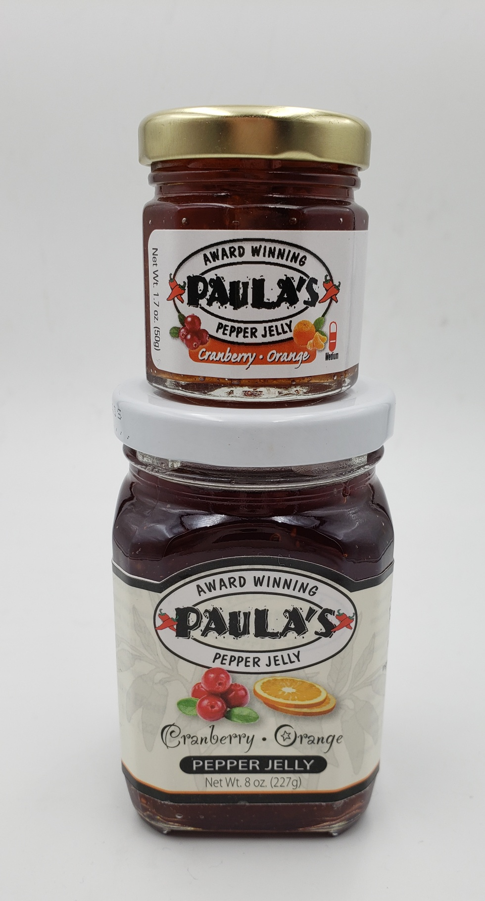 1.7 oz. orange and cranberry pepper jelly jar on top of the 8 oz. Paula's Pepper Jelly jar label out.