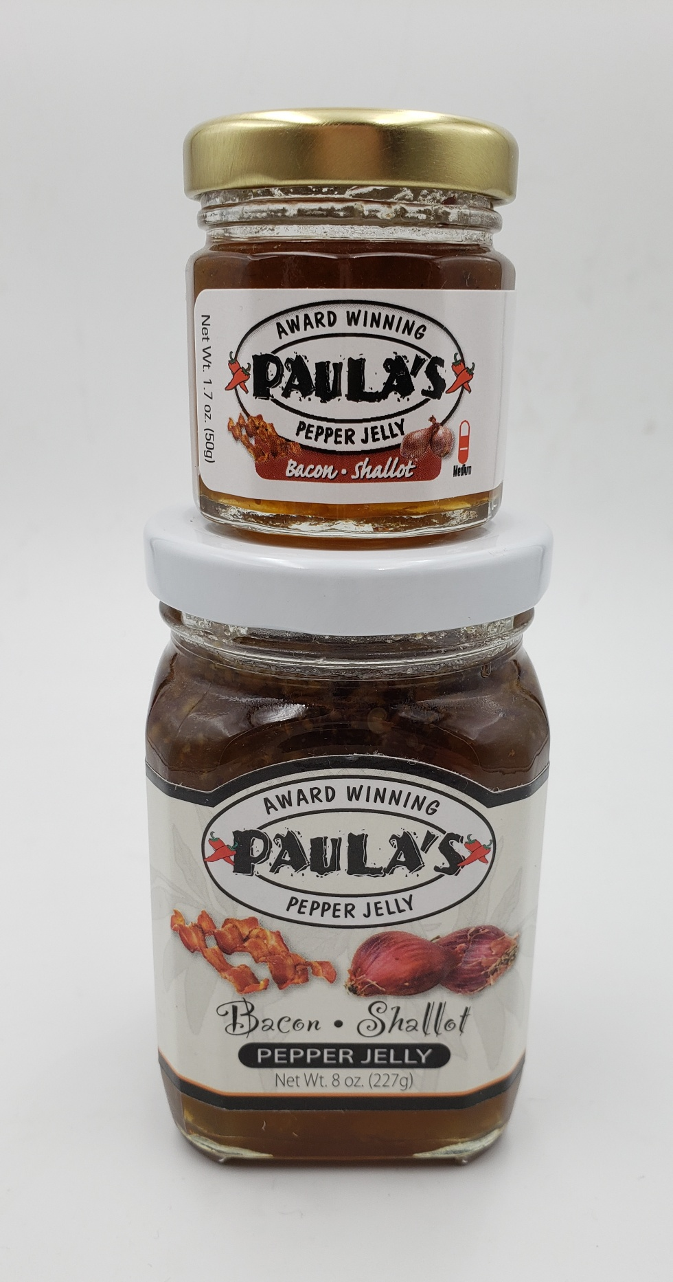 1.7 oz. organic jelly jar from Paula's Pepper Jelly on top of an 8 oz. pepper jelly jar label-side out.