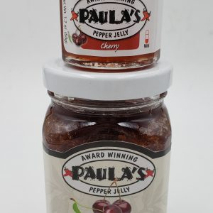 One of Paula's 1.7 oz. pepper jelly jars stacked on top of the 8 oz. best pepper jelly jar from Paula's Pepper Jelly.