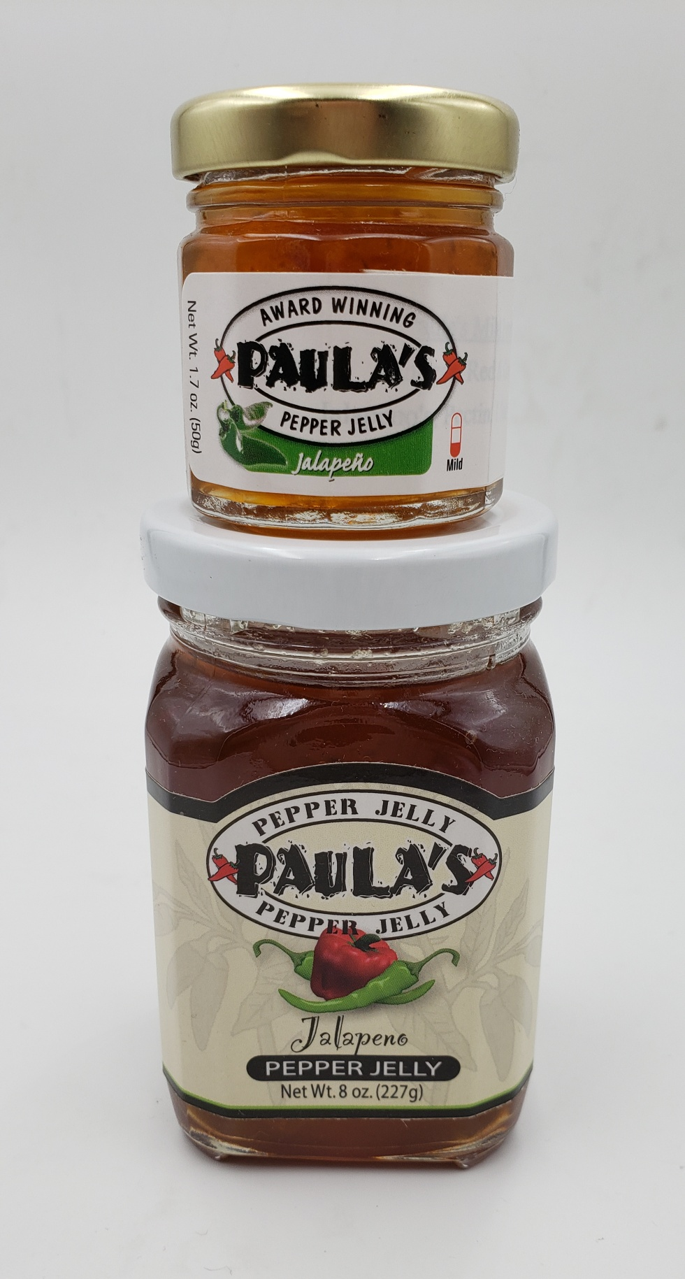 The 1.7 oz. Paula's Pepper Jelly Jar on top of the 8 oz. Jalapeno Pepper Jelly both label out.