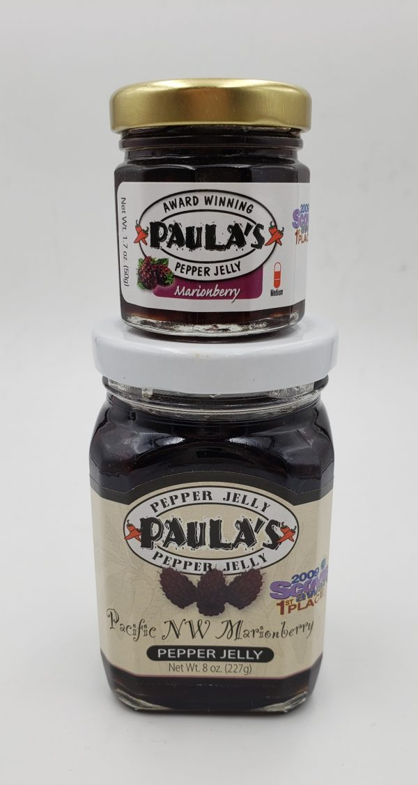 The 1.7 oz. marionberry pepper jelly jar on top of the 8 oz. Paula's Pepper Jelly jar both full of marionberry pepper jelly.