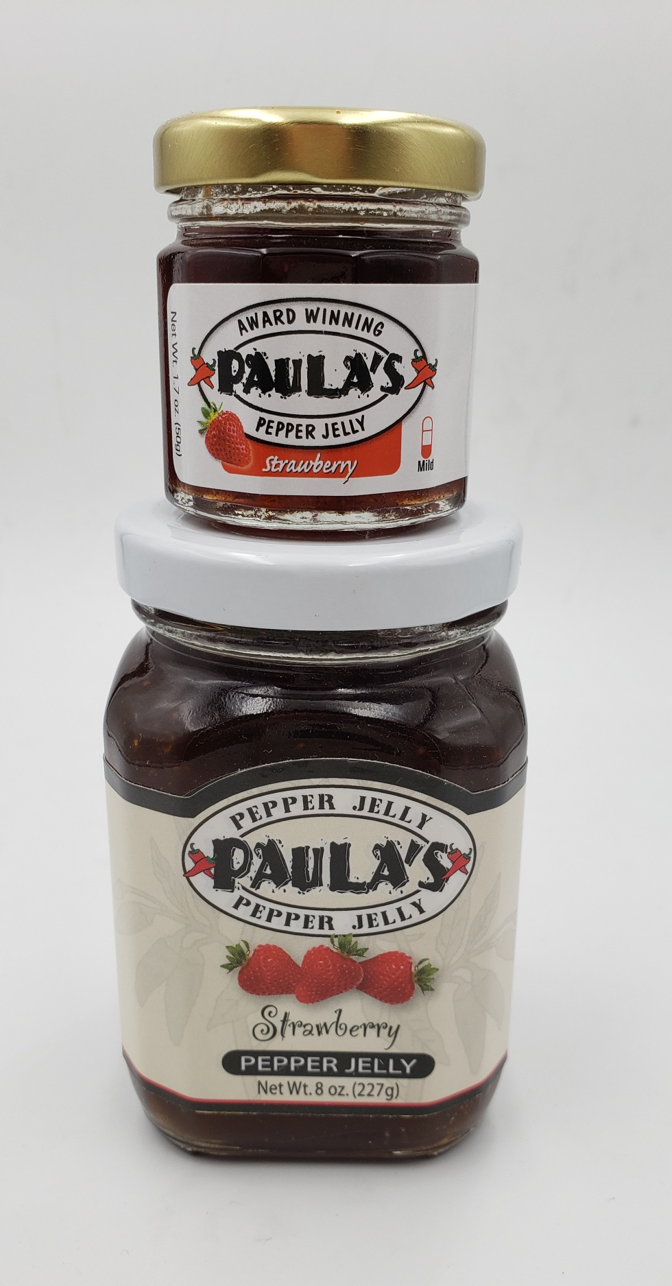 1.7 oz. strawberry pepper jelly jar on top of the 8 oz. Paula's Pepper Jelly jar label-out.