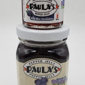 1.7 oz. wild blue huckleberry pepper jelly jar on top of the 8 oz. Paula's Pepper Jelly jar. Both are full of Paula's Wild Blue Huckleberry Pepper Jelly.