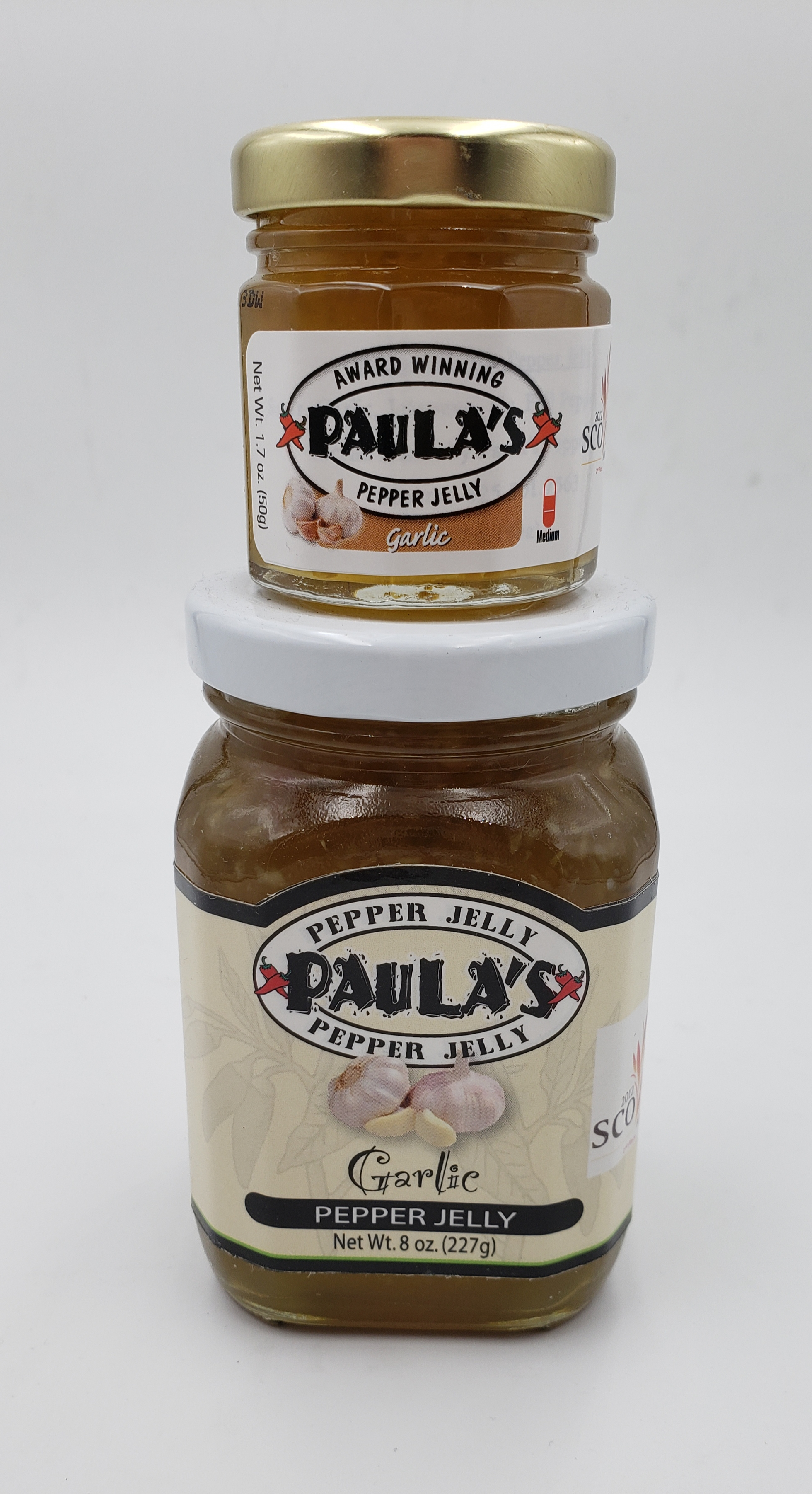 1.7 oz. Paula's Pepper Jelly jar filled with garlic pepper jelly on top of an 8 oz. jar of organic jelly label side out.