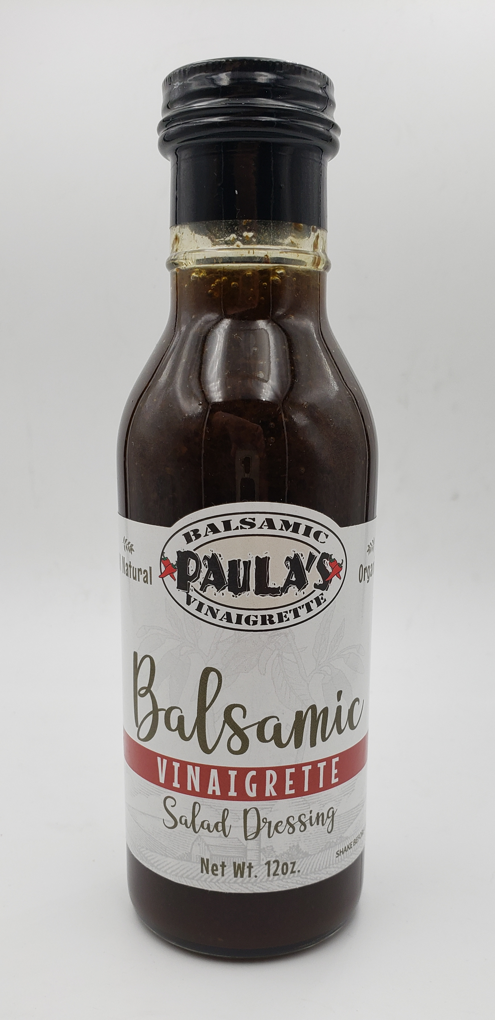 12 oz. bottle of Paula's homemade balsamic vinaigrette salad dressing from Paula's Pepper Jelly with the label facing out.