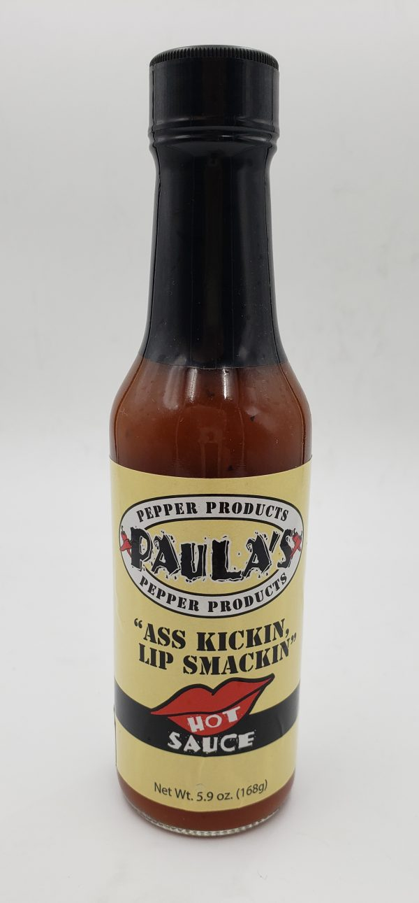 "Close-up of Paula's organic hot sauce at Paula's Pepper Jelly label side out. The label reads, ""Paula's Ass Kickin Lip Smackin Hot Sauce."""
