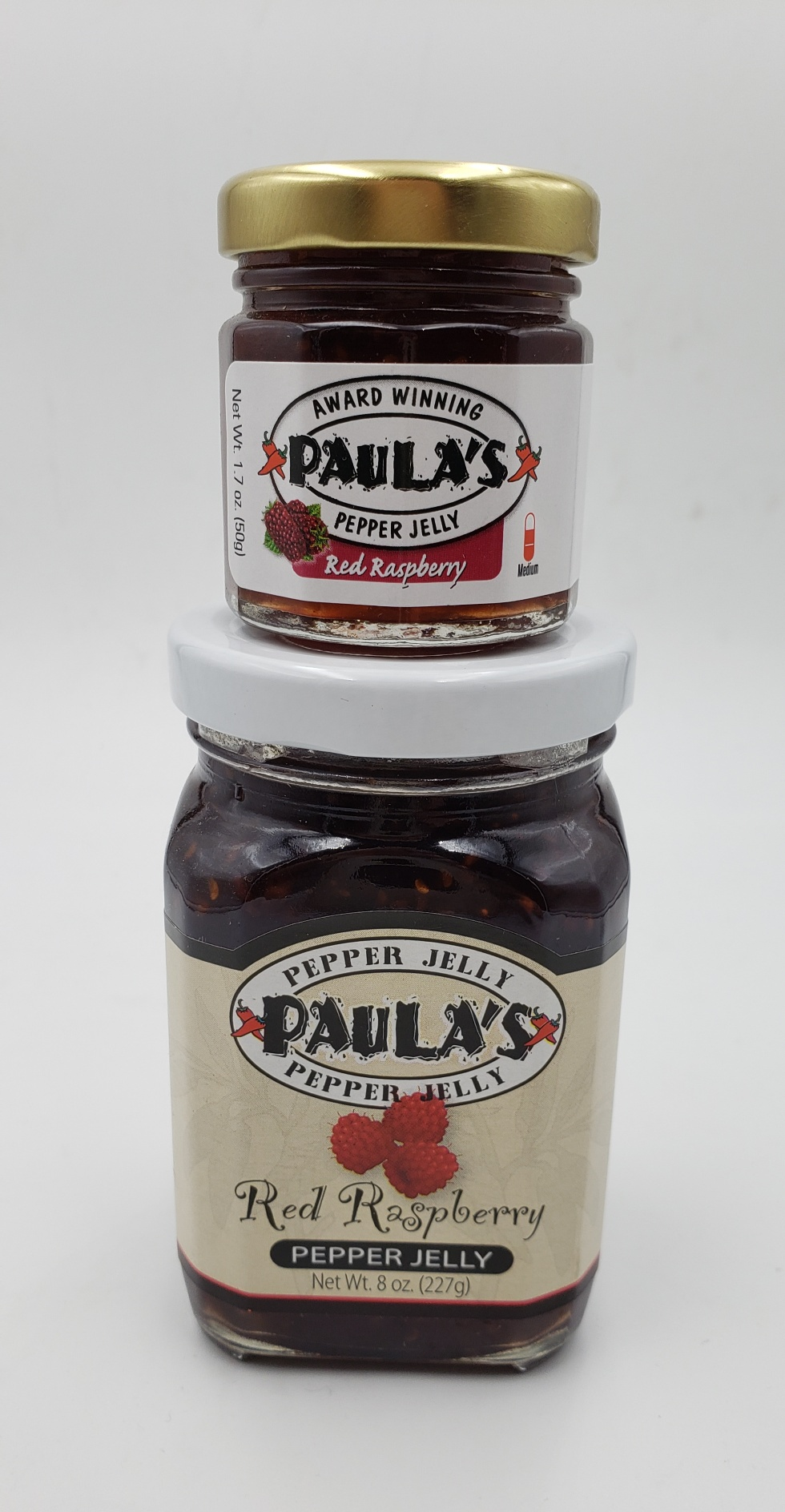 1.7 oz. Paula's Pepper Jelly jar on top of the 8 oz. Paula's Red Raspberry Pepper Jelly jar. Both are label out and full of pepper jelly.